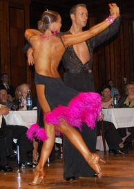 Latin dancers in their costumes. The woman is wearing backless dress with deep slits on its lower portion, while the man is wearing a shirt with top buttons open.