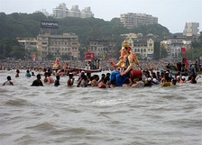 Large statue of Ganesh on the water, surrounded by people