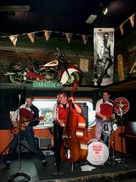 Gazzguzzlers use the classic instruments associated with rockabilly: a hollow-body guitar, and upright bass, and a pared-down drum kit.