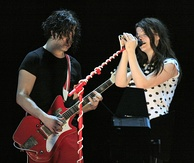 On the left, a man in red pants and a black T-shirt with black hair down to his chin holding a red guitar. On the right, a woman wearing a white shirt with black polka dots standing behind a red microphone stand.