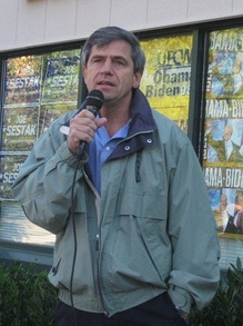 "A gray-haired man wearing a green jacket speaks into a microphone outside in front of a building, with campaign signs that read ""Joe Sestak"" and ""Obama-Biden"" in the background."