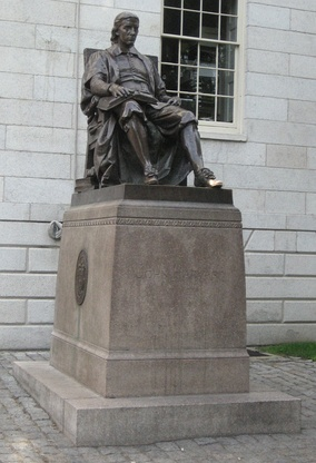 "John Harvard guard­ing the Univer­sity Hall offices of the Dean of Harvard College (the loca­tion calcu­lated, the Harvard Crimson once said, ""accord­ing to one theory, in order to keep all light out of the Dean's office"").​[26] Note Harvard College seal on plinth."