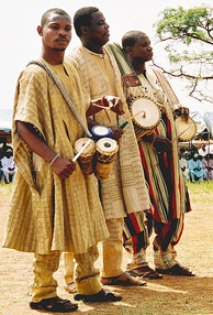 Yoruba drummers: One holds omele ako and batá, the other two hold dunduns.