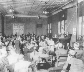 The first day of the trial. Spectators were racially segregated. The stenographer can be seen next to Newt Lee, who is being questioned by prosecutor Hugh Dorsey.