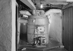 "A photo of an ""octopus""-type hot-air furnace in a basement."
