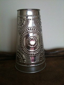 A 21st-century reproduction barn lantern made of punched tin.