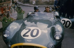 Tony Brooks parked outside the 1957 Le Mans Aston Martin base, the Hotel de France, at the wheel of his DBR1 race car.