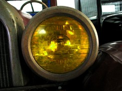 "One of the first optical headlamp lenses, the Corning Conaphore. Selective yellow ""Noviol"" glass version shown."