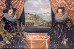 A man and a woman standing at a table near a window