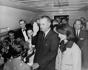 Cecil Stoughton's iconic photograph of Lyndon B. Johnson being sworn in as U.S. President aboard Air Force One, Love Field, Dallas. Jacqueline (right), still in her blood-soaked clothes (not visible in picture), looks on.