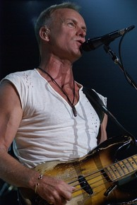 A man in a white shirt standing behind a microphone stand and holding a guitar