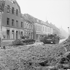 A Valentine Mk XI Royal Artillery OP tank (left) and a Churchill tank (right) in Goch, 21 February 1945