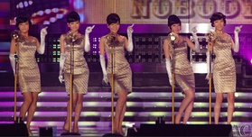 Five women with beehive hairstyles wearing matching golden sheath dresses and elbow-length gloves