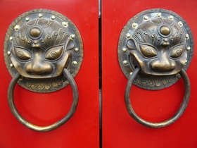 A traditional red Chinese door with Imperial guardian lion knocker