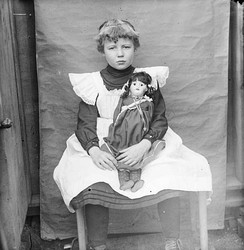 A girl and her doll in the 1900s.