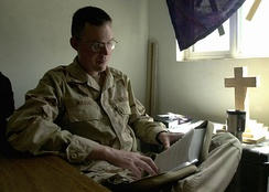 A U.S. Navy chaplain in Iraq studies his Bible for an upcoming service.