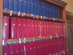 The 2013 Norwegian hymnal on a shelf at Meland Church. The red volumes are the standard edition and the blue ones are the large-print edition.