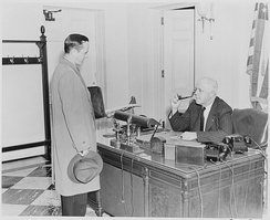 White House receptionist William Simmons at his desk in 1946, conversing with a visitor