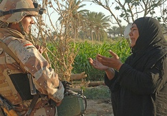 A woman pleads with an Iraqi army soldier from 2nd Company, 5th Brigade, 2nd Iraqi Army Division to let a suspected insurgent free during a raid near Tafaria, Iraq