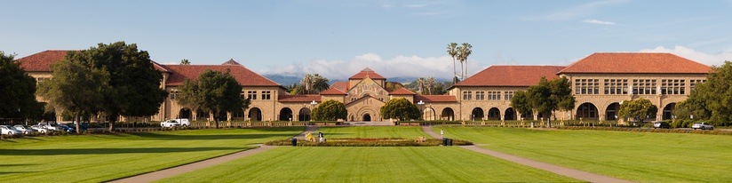View of the main quadrangle of Stanford with Memorial Church in the center background from across the grass-covered Oval.