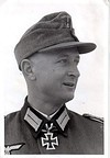 A man wearing a military uniform and field cap with an Iron Cross displayed at the front of his uniform collar.