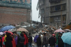 Rain was among the many problems affecting the area in the aftermath of the earthquake. Here, a group of onlookers examine a collapsed building in the rain.