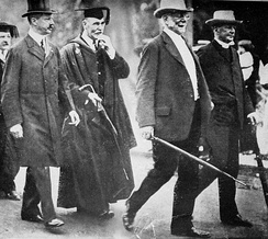 (l-r) US Navy Secretary (and Har­vard Over­seer) George Meyer; Prof. Frank W. Taussig; Pres. Eliot (who dis­dained aca­dem­ic regal­ia);[2] Bishop (and Over­seer) William Lawrence (1911)