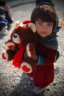A young Afghan girl clenches her teddy bear that she received at a medical clinic at Camp Clark in Khost Province.
