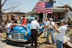 President Barack Obama greets an 85-year-old tornado survivor in front of his house on May 29, 2011.