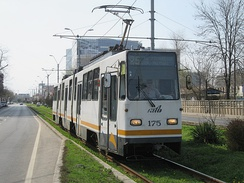 A V3A tram running down tracks embedded in grass on the Timișoara Boulevard in Bucharest, Romania