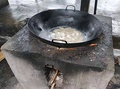 A wok on an outdoor wood stove