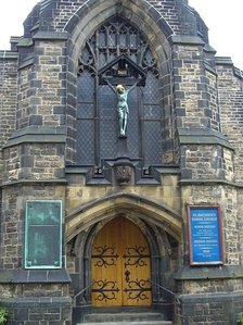 The main entrance on Carver Street with the War Memorial plaque to the left and Crucifixtion statue above.