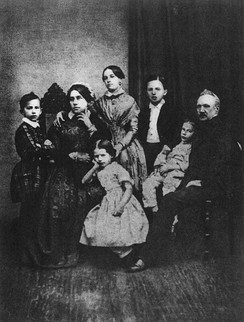 A family portrait, with the mother on the left and the father on the right surrounded by four children.