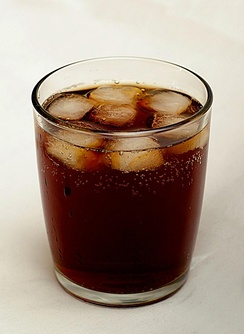 A glass of cola served with ice cubes