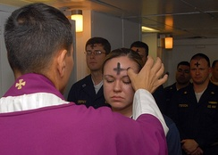 A priest marks a cross of ashes on a worshipper's forehead, the prevailing form in English-speaking countries.[26]