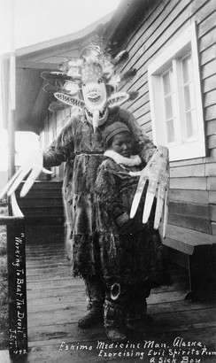 Yup'ik shaman (angalkuq) exorcising evil spirits (caarrluk) from a sick boy. The enormous wooden hands with shortened thumbs (inglukellriik unatnquak ayautaunatek) worn by the shaman. Nushagak Bay, ca. 1890s[30]