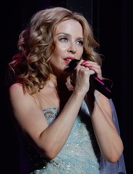 "In 1988, Kylie Minogue went to number one with her debut UK single ""I Should Be So Lucky"", and achieved three more number ones, including as a part of Band Aid II."