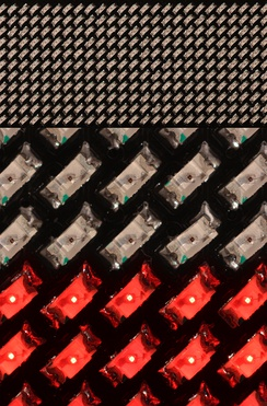 Composite image of a 11x44 LED matrix lapel name tag display using 1608/0603-type SMD LEDs. Top: A little over half of the 21x86 mm display. Center: Close-up of LEDs in ambient light. Bottom: LEDs in their own red light.