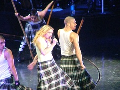 A blond woman with long wavy hair singing on stage, wearing a white T-shirt and a black-and-white patterned skirt, holding a microphone in her hand. She is surrounded by dancers in similar attire, carrying long poles.