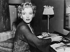 Monroe, wearing a transparent lace robe and diamond earrings, sitting at a dressing table and looking off-camera with a shocked expression