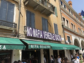 """No Mafia Venezia è Sacra"" (No Mafia Venice is Sacred) banner hanging over a restaurant in Venice across from the Rialto Bridge in 2019."