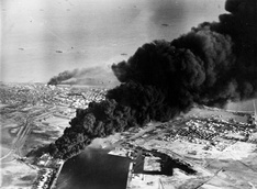 Smoke rises from oil tanks beside the Suez Canal hit during the initial Anglo-French assault on Egypt, 5 November 1956