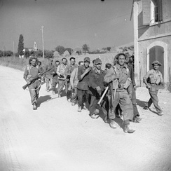 German prisoners being marched into captivity by men of the Queen's Royal Regiment, 56th Division, Montefiore area, 13 September 1944.