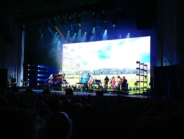 "The Rascals performing ""Groovin'"" during their 2013 Once Upon a Dream show, with a peaceful park scene showing on the video screen behind them. Gene Cornish plays the well-known harmonica part."