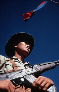Viet Cong soldier stands beneath a Viet Cong flag carrying his AK-47 rifle. He was participating in the exchange of POWs by the International Commission of Control and Supervision.