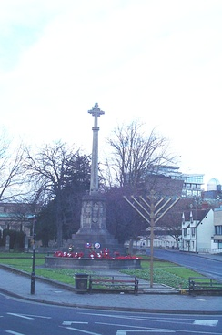 The cross of the war memorial (Church of England) and a menorah (Judaism) coexist at the north end of St Giles' in Oxford, England