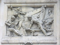 A relatively modern high relief (depicting shipbuilding) in Bishopsgate, London. Note that some elements jut out of the frame of the image.