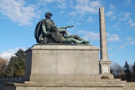 A monumental obelisk surrounded by sculptures of soldiers at the Soviet military cemetery in Warsaw