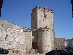 Coria castle. Basically a large square keep, but with several smaller round towers jutting out on all side.