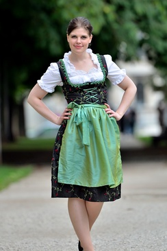 Woman wearing modern dirndl with mid-length skirt.